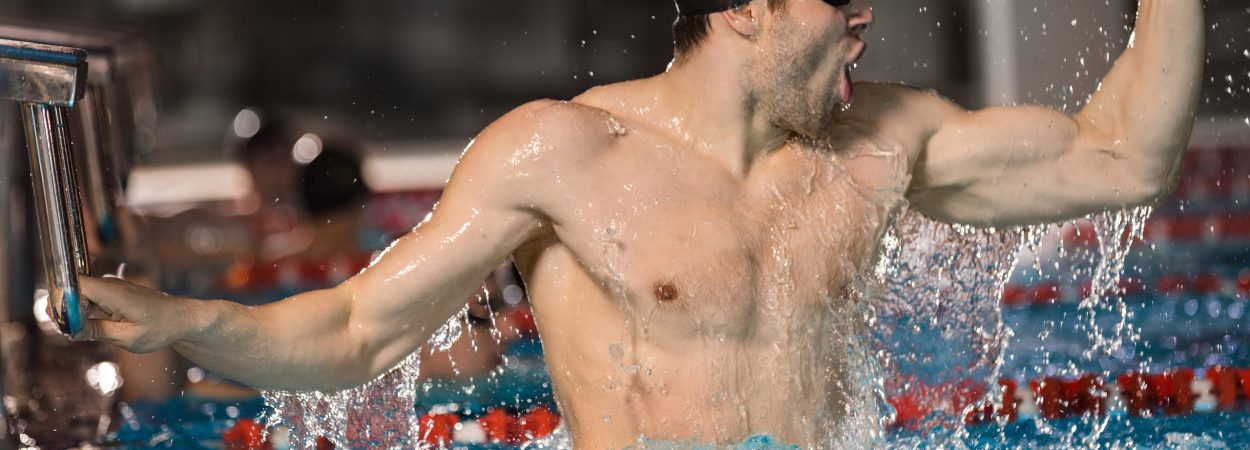 Happy male swimmer holding starting block at the edge of a pool and celebrating